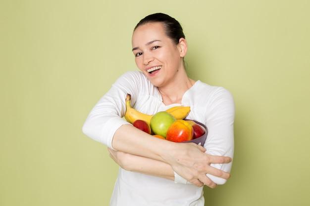 Giovane donna attraente in camicia bianca che sorride e che mostra la ciotola di frutta