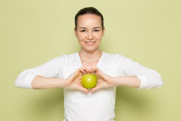 Giovane donna attraente in camicia bianca che tiene mela verde