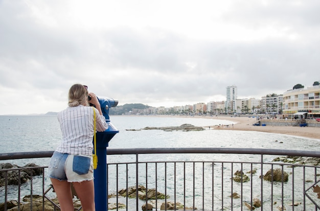 Giovane donna attraente in camicia bianca e con una piccola borsa gialla che guarda su un mare in un giorno soleggiato in binoculare su una spiaggia di lloret de mar, costa brava, spagna. sguardo della donna in telescopio turistico.
