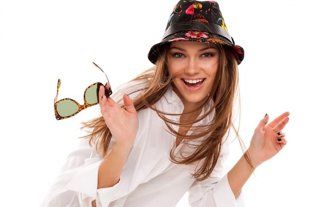 Giovane donna attraente in camicia e occhiali da sole
