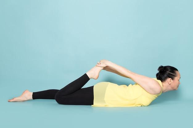 Giovane donna attraente in camicia gialla e pantaloni neri facendo posture yoga