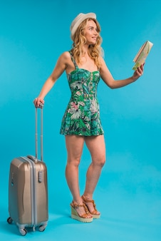 Giovane donna attraente in cappello che tiene mappa e valigia