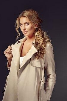 Giovane donna attraente in cappotto beige che guarda l'obbiettivo