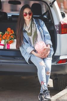 Giovane donna attraente in macchina con scatola regalo, regalo e fiori. bella signora in primavera con bouquet di tulipani. femmina in automobile.