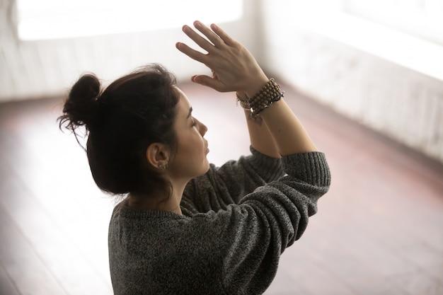 Giovane donna attraente in maglione grigio che fa namaste
