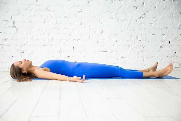 Giovane donna attraente in posa del corpo morto, backgroun studio bianco
