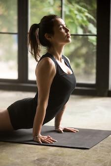 Giovane donna attraente in posa di urdhva mukha svanasana