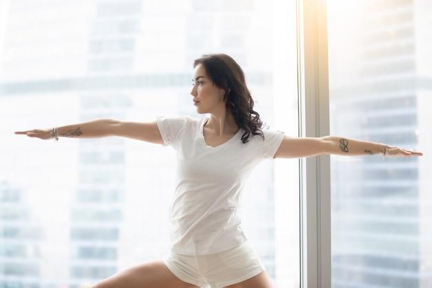 Giovane donna attraente in posa di warrior two, contro la finestra