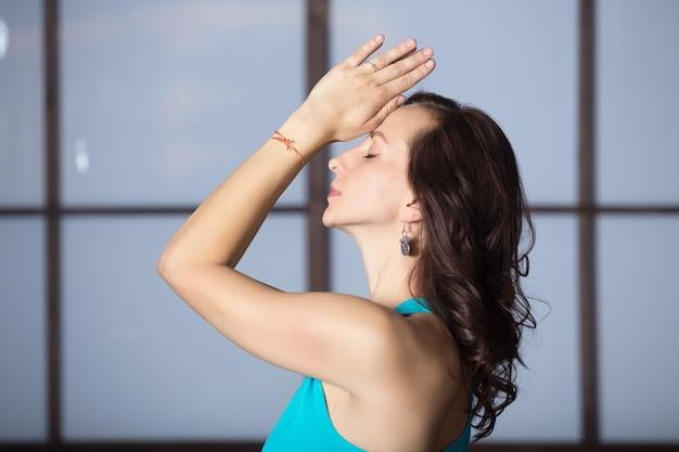 Giovane donna attraente in posa di yoga, pratica di sera studio