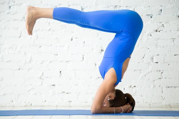 Giovane donna attraente in posa headstand, backgroun studio bianco