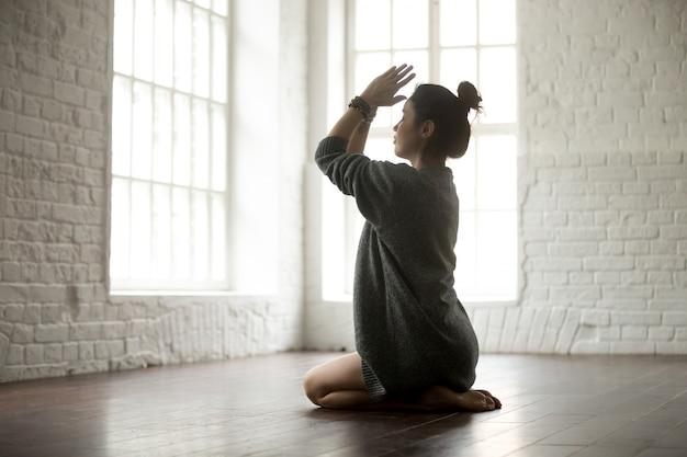 Giovane donna attraente in posa vajrasana, studio loft bianco