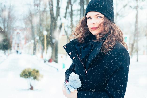 Giovane donna attraente in un cappotto sulla strada durante una nevicata