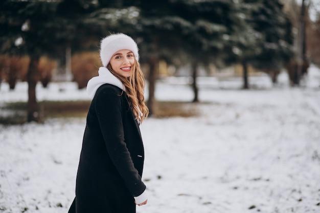 Giovane donna attraente in un parco d'inverno in un cappello carino