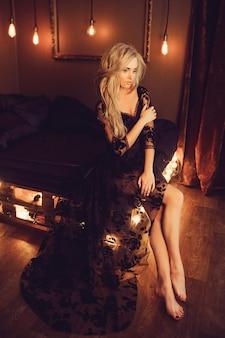 Giovane donna attraente in veste da camera nero che posa sul letto