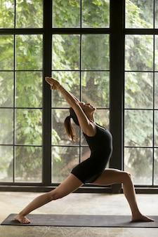 Giovane donna attraente in warrior un esercizio