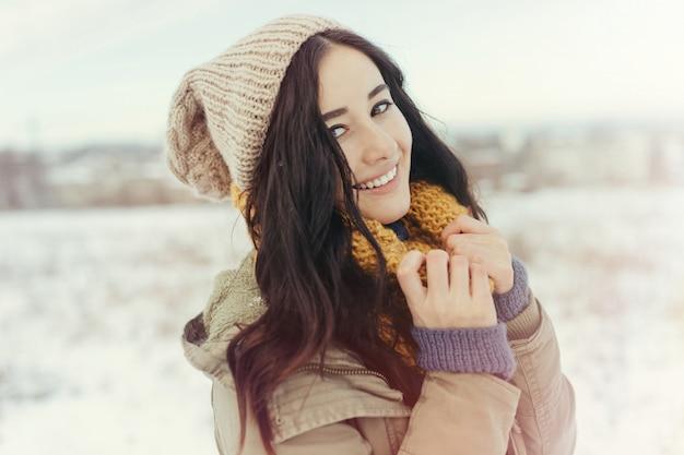 Giovane donna attraente nell'orario invernale all'aperto