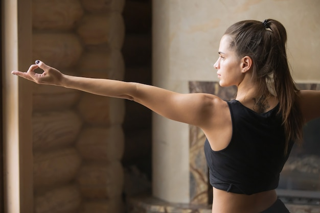 Giovane donna attraente nella posa del guerriero due, backgr interno domestico