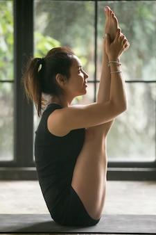 Giovane donna attraente nella posa di urdhva mukha paschimottanasana