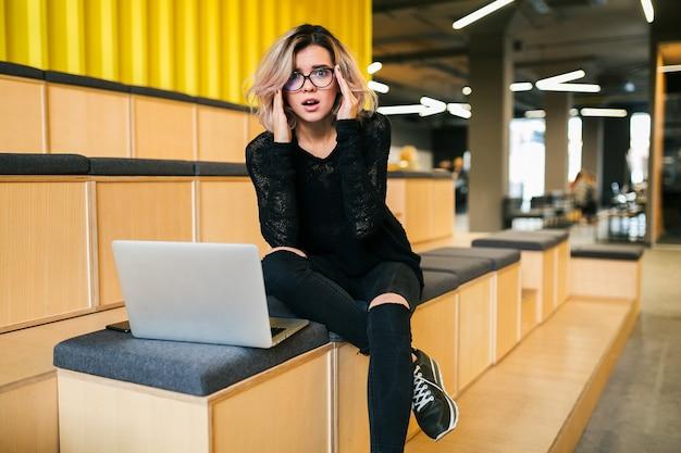 Giovane donna attraente seduta in aula, con stress, lavorando al laptop, con gli occhiali, auditorium moderno, formazione studentesca online, libero professionista, occupato, mal di testa, espressione del viso frustrato