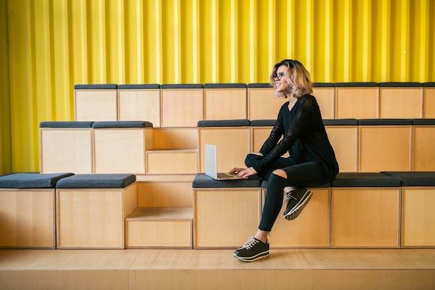 Giovane donna attraente seduta in aula, lavorando al computer portatile, con gli occhiali, auditorium moderno, formazione studentesca online, libero professionista, sorridente, avvio adolescente, guardando nella fotocamera, felice