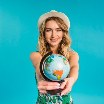 Giovane donna attraente sorridente in cappello e vestito che mostrano globo