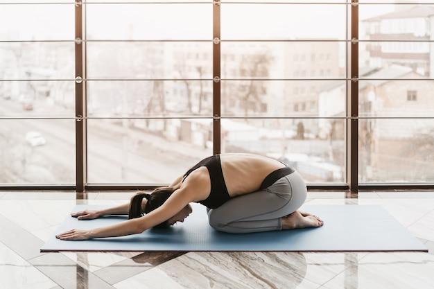 Giovane donna attraente sottile con capelli lunghi praticare yoga al chiuso.