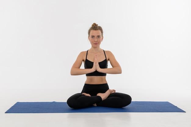 Giovane donna attraente sportiva che fa pratica di yoga su fondo bianco. sukhasana.