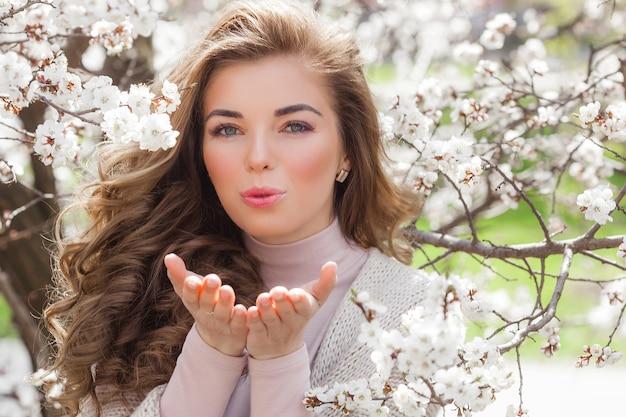 Giovane donna attraente su sfondo di primavera con fiori. chiuda sul ritratto di bella ragazza compone. signora all'aperto in giardino