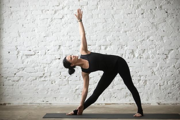 Giovane donna attraente yogi a utthita trikonasana posa, bianco l