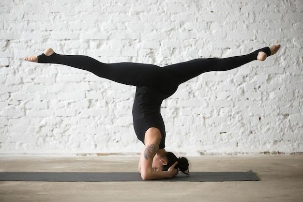 Giovane donna attraente yogi che fa salamba sirsasana posa con sp