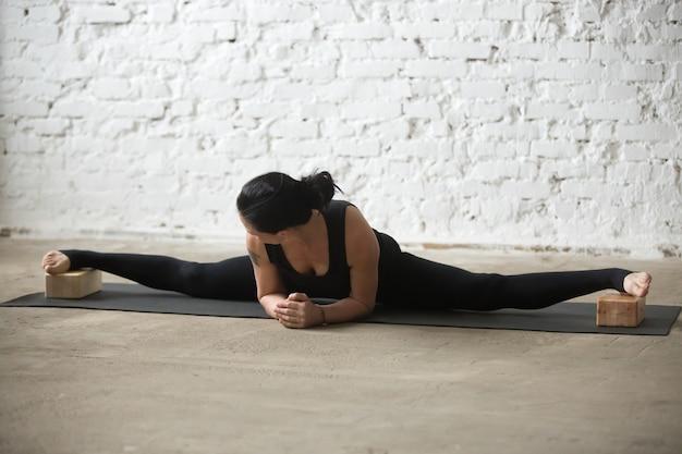 Giovane donna attraente yogi in avanzata samakonasana posa con b