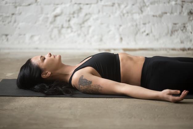 Giovane donna attraente yogi in posa di savasana, loft background, c
