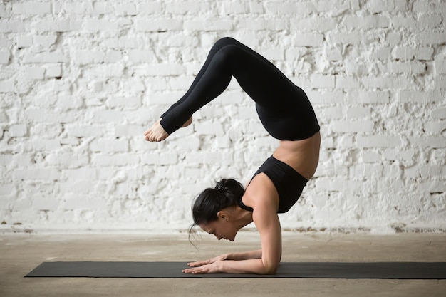 Giovane donna attraente yogi in vrischikasana posa, loft bianco ba