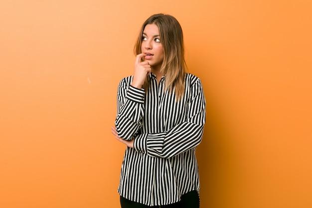 Giovane donna autentica carismatica contro un muro rilassato pensando a qualcosa