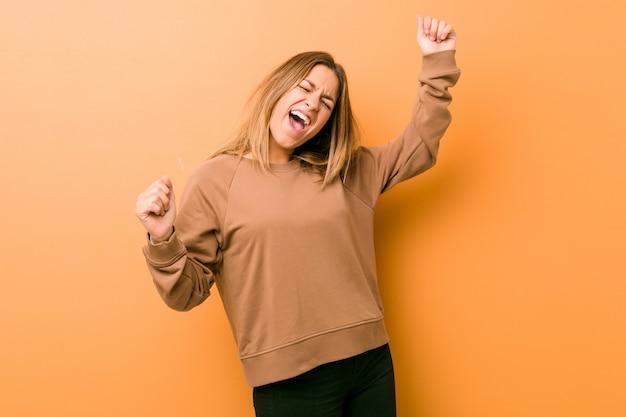Giovane donna autentica carismatica vera gente contro un muro che celebra un giorno speciale, salta e alza le braccia con energia.