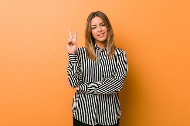 Giovane donna autentica carismatica vera gente contro un muro che mostra il numero due con le dita.