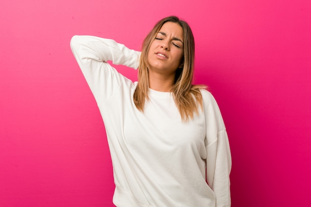 Giovane donna autentica carismatica vera gente contro un muro che soffre di dolore al collo a causa dello stile di vita sedentario.