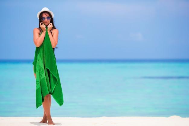 Giovane donna avvolta in un asciugamano sulla spiaggia di sabbia bianca