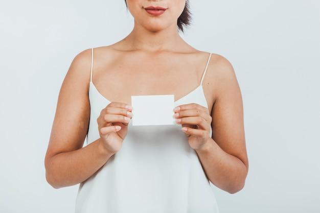 Giovane donna azienda biglietto da visita con entrambe le mani