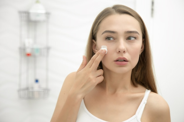Giovane donna bella applicando crema a faccia in bagno