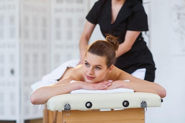Giovane donna bella durante il massaggio sulla schiena nel salone spa.