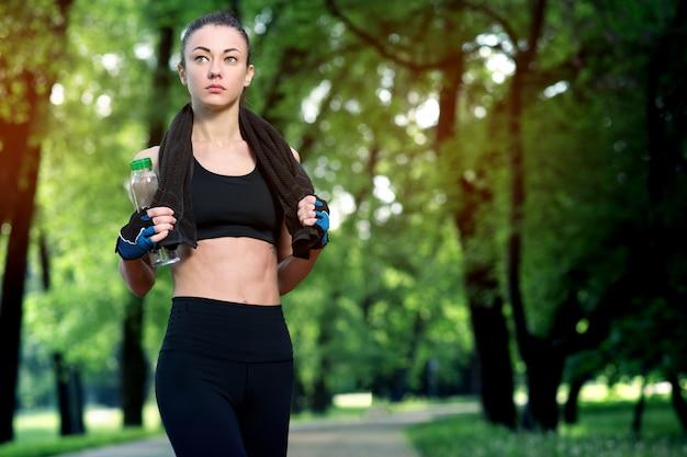 Giovane donna bella e forte che riposa dopo un allenamento attivo presso il parco estivo. concetto di sport. uno stile di vita sano