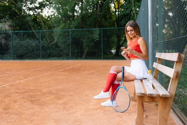 Giovane donna bellissima sport rilassante con acqua in panchina presso il campo da tennis dopo la partita