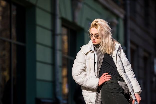 Giovane donna bionda alla moda che posa all'aperto