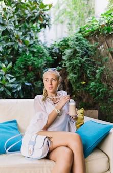 Giovane donna bionda alla moda che si siede sul sofà con le gambe attraversate che tengono vetro del macchiato del latte