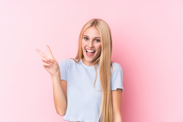Giovane donna bionda allegra e spensierata che mostra un simbolo di pace con le dita
