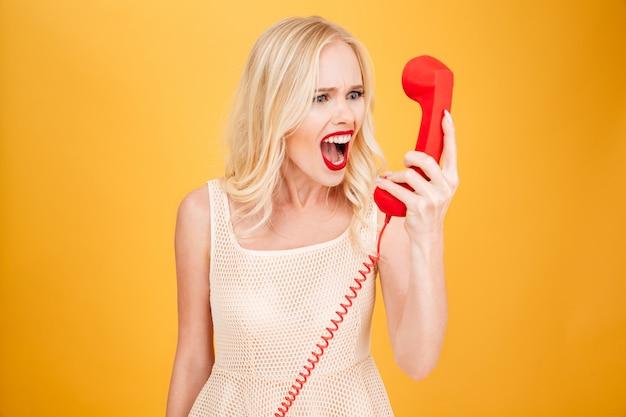 Giovane donna bionda arrabbiata di grido che parla per telefono.