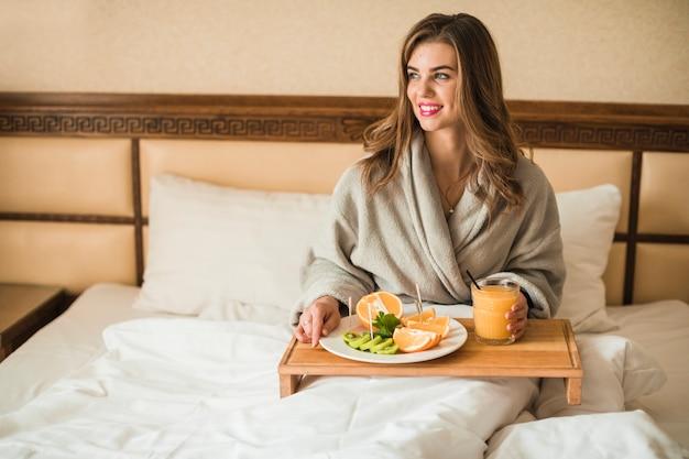 Giovane donna bionda bellezza facendo colazione sul letto al mattino presto
