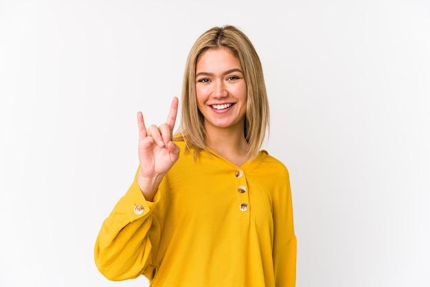 Giovane donna bionda caucasica isolata che mostra un gesto di corna