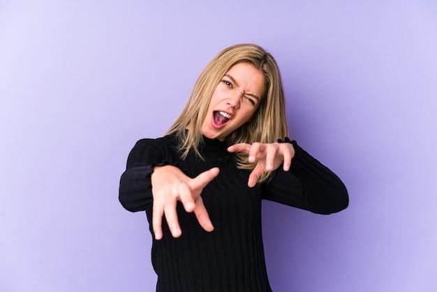 Giovane donna bionda caucasica isolato mostrando artigli imitando un gatto, gesto aggressivo.